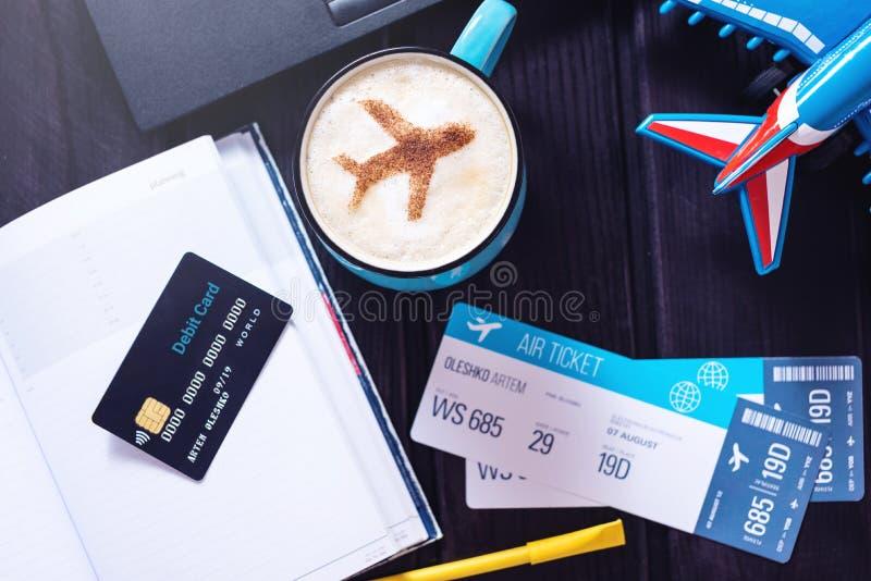 Bärbara datorn plana biljetter, kaffe, kreditkort ligger på tabellen royaltyfri foto