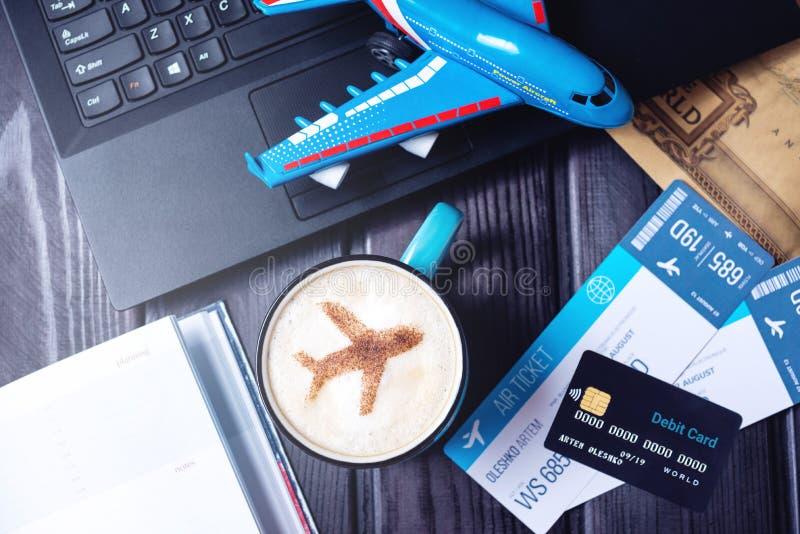 Bärbara datorn plana biljetter, kaffe, kreditkort ligger på tabellen arkivfoton