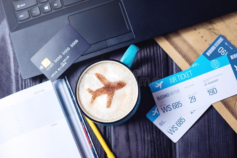 Bärbara datorn plana biljetter, kaffe, kreditkort ligger på tabellen fotografering för bildbyråer