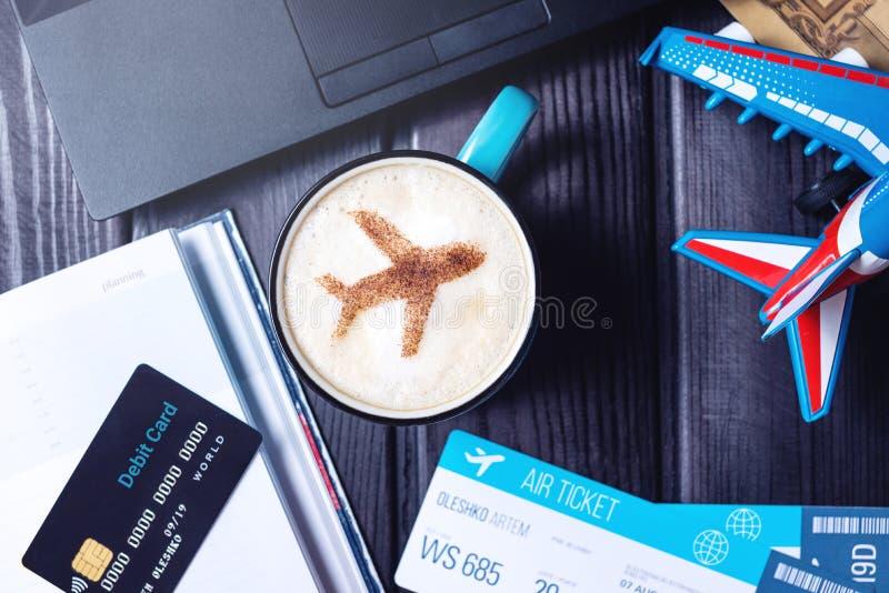 Bärbara datorn plana biljetter, kaffe, kreditkort ligger på tabellen royaltyfria bilder