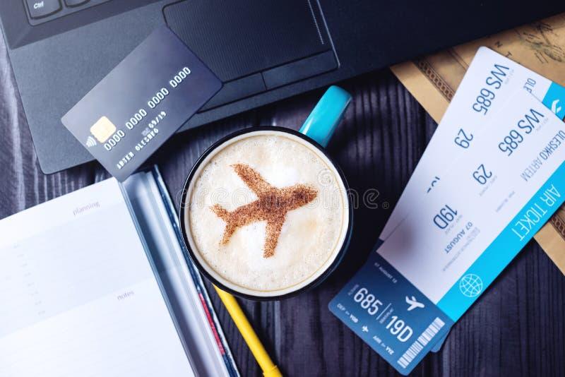 Bärbara datorn plana biljetter, kaffe, kreditkort ligger på tabellen royaltyfri bild