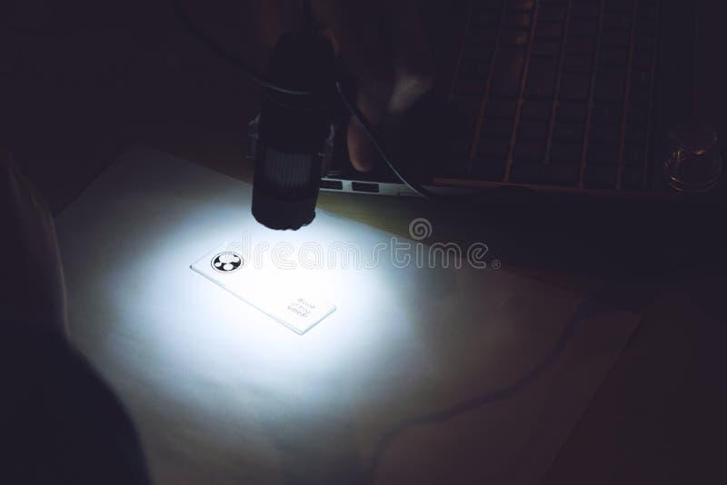 Bärbart USB Digital mikroskop förbindelse till en bärbar dator Mannen undersöker det biologiska silkespappret royaltyfri bild