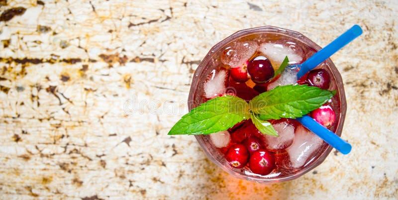 Bärcoctail i exponeringsglas med is och mintkaramellen på den gamla tabellen Fritt avstånd för text royaltyfri fotografi