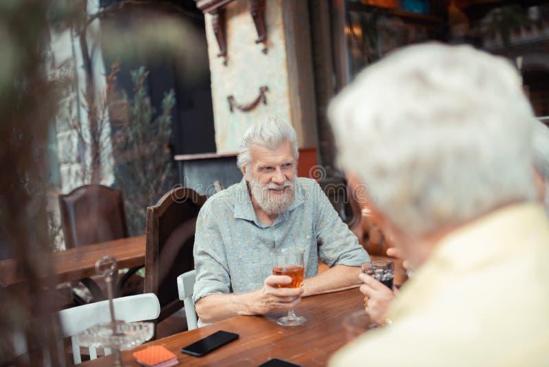 Bärgad gråhårig man som dricker alkohol med vänner royaltyfri foto