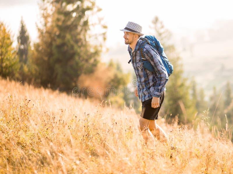 Bärgad turistman i hatt med ryggsäck som vandrar i bergsområden, manliga kejsar från Kaukasien utomhus royaltyfria foton