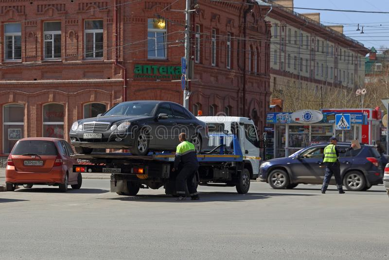 Bärgningsbilen tar bilen av infringeren av regler av trafik royaltyfri bild