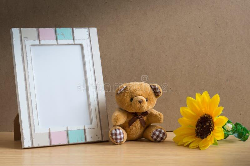 Bärnpuppe mit Fotorahmen und -sonnenblume lizenzfreie stockfotografie