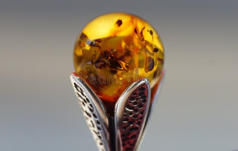 Bärnstensfärgad boll i en silverram arkivfoto