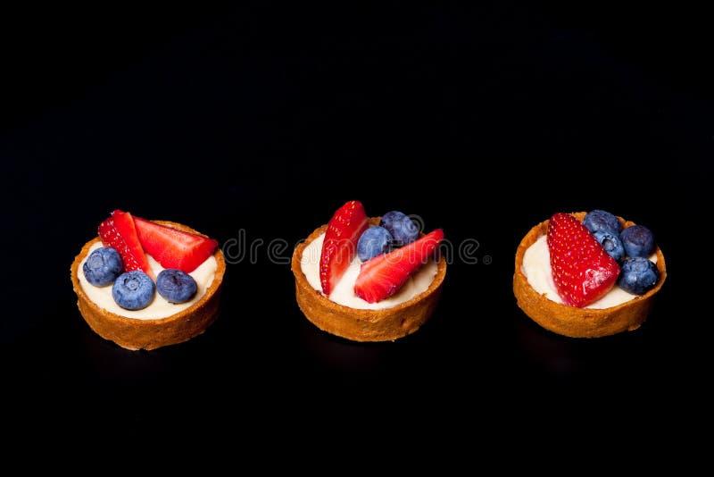 Bärtartlets med blåbär, jordgubbar och smör lagar mat med grädde arkivbild