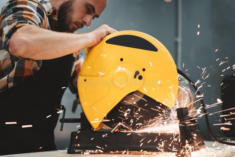 Bärtige Arbeitskraft, die elektrische Schleifmaschine in der Tankstelle verwendet Arbeit in der Aktion Funken fliegen auseinander lizenzfreie stockfotos