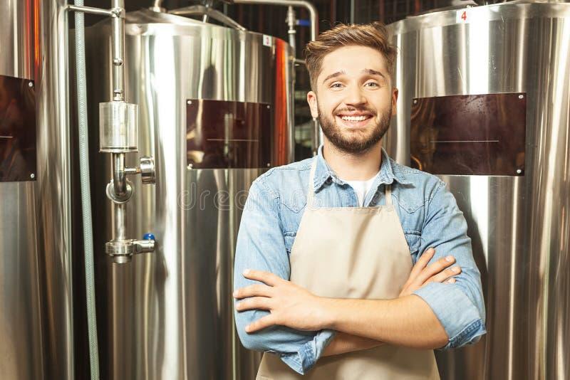 Bärtige Arbeitskraft mit den gekreuzten Händen an der Bierfabrik lizenzfreie stockfotos