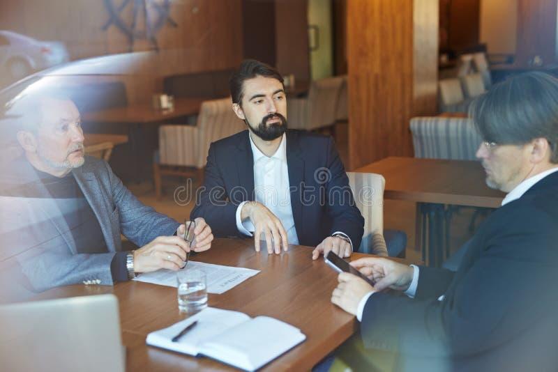 Bärtige Unternehmer, die Verhandlungen leiten lizenzfreies stockfoto