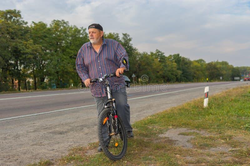 Bärtiger älterer Mann auf dem Straßenrand, der fertig wird, auf Fahrrad zu fahren lizenzfreie stockbilder