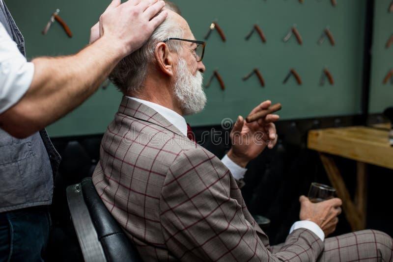Bärtiger alter Geschäftsmann, der am Friseursalon im Stuhl wählt Haarschnittentwurf sitzt lizenzfreies stockfoto