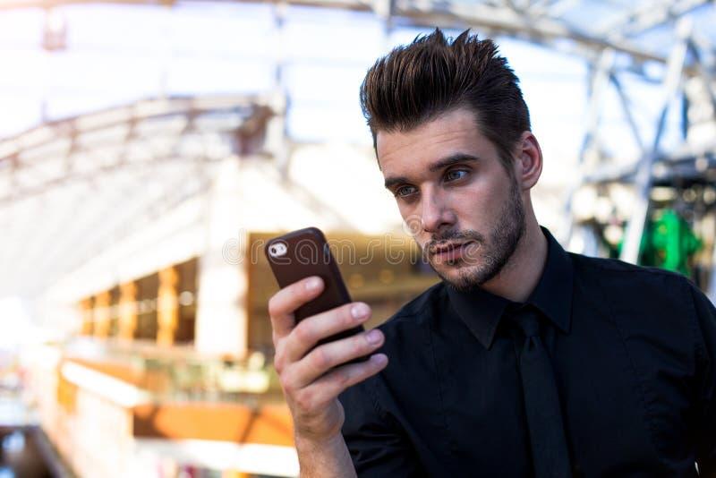 Bärtiger Berufsbanker, der Mobiltelefon verwendet stockbilder