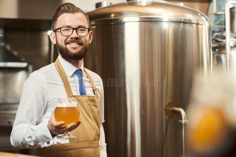 Bärtiger Brauer, der Glas des kalten Bieres mit Schaum hält stockfotografie