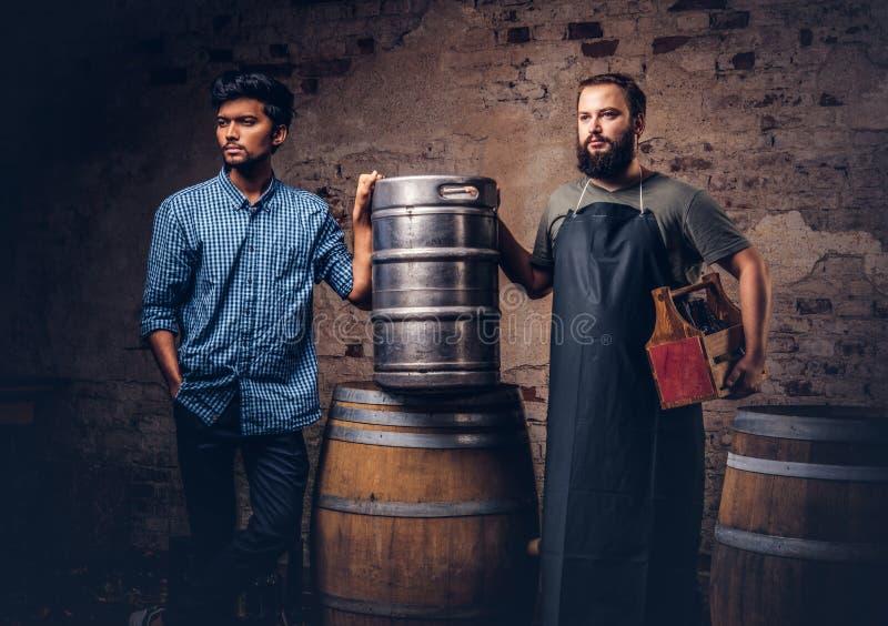 Bärtiger Brauer und sein Freund, die nahe Fässer an der alten Brauereifabrik steht stockbild