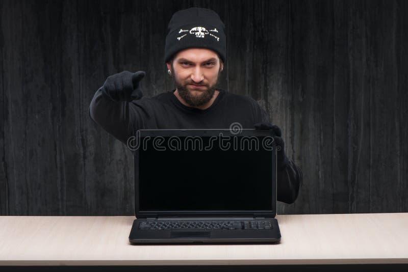 Bärtiger Computerhacker mit einem Laptop stockbild