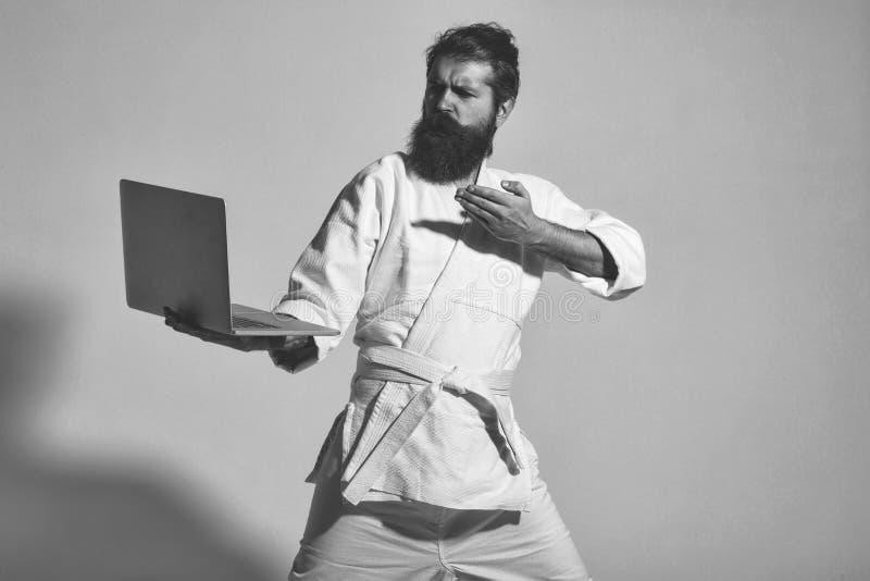 Bärtiger ernster Karatemann im Kimono mit Laptop stockfotos