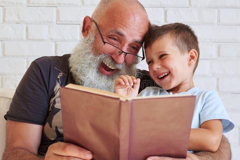 Bärtiger gealterter Mann und sein Enkel, die den Spaß liest ein Buch toge hat lizenzfreie stockfotografie