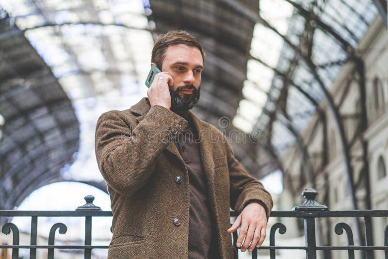 Bärtiger Geschäftsmann, der Anruf an seinem Handy macht Zufälliger Berufsunternehmer, der Smartphone an der Halle des Zugs verwen lizenzfreies stockfoto