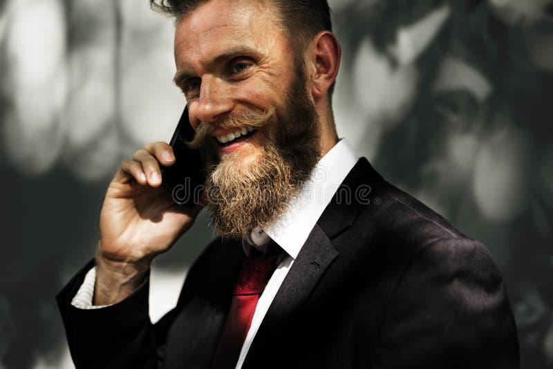 Bärtiger Geschäftsmann, der Handy verwendet