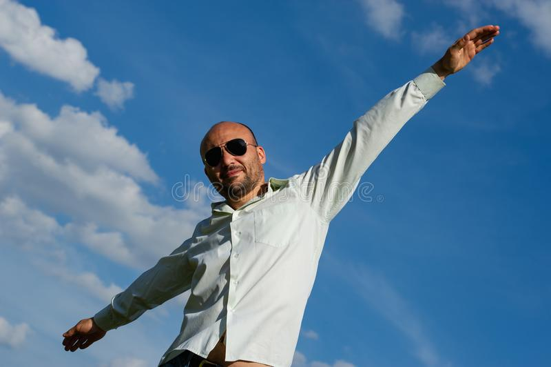 Bärtiger Geschäftsmann mit der Sonnenbrille, die seine Arme gegen ausdehnt stockfoto
