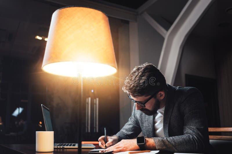 Bärtiger Geschäftsmann sitzt indem den Holztisch mit Lampe und das Arbeiten auf neuem Startprojekt in Dachboden ofiice nachts lizenzfreie stockfotos