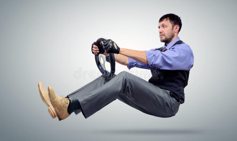 Bärtiger Geschäftsmannautofahrer mit einem Lenkrad stockbild