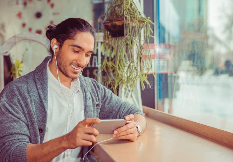 Bärtiger glücklicher Mann, der das Telefonlächeln betrachtet lizenzfreie stockbilder