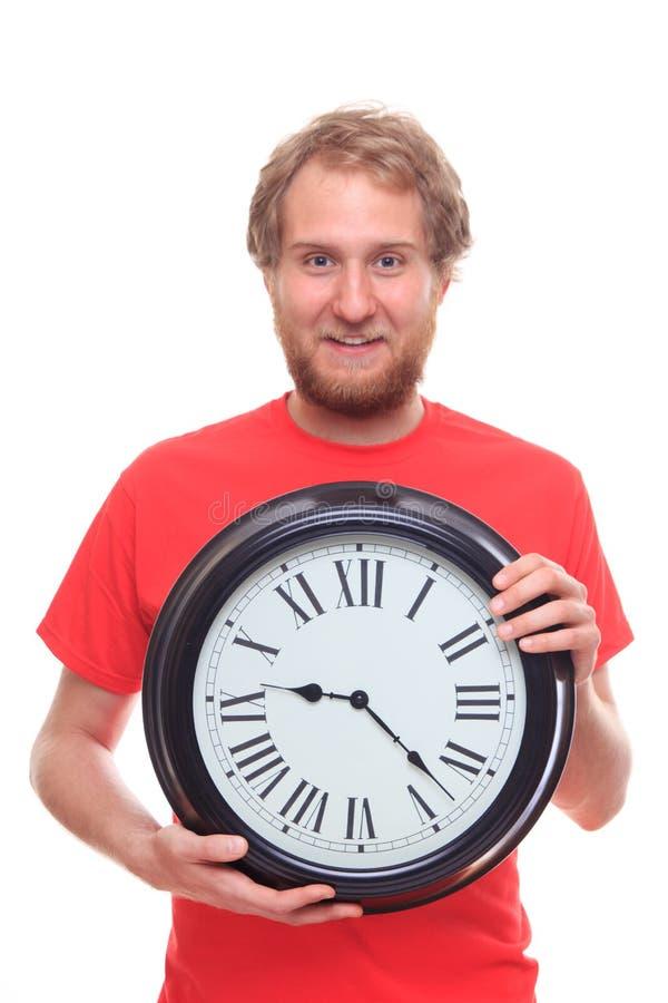 Bärtiger glücklicher Mann, der große Uhr und das Lächeln hält lizenzfreie stockbilder