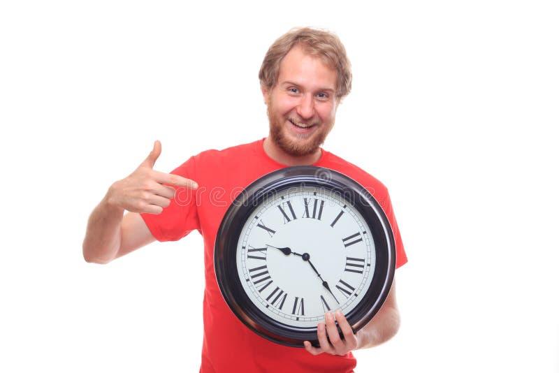 Bärtiger glücklicher Mann, der große Uhr und das Lächeln hält lizenzfreies stockfoto