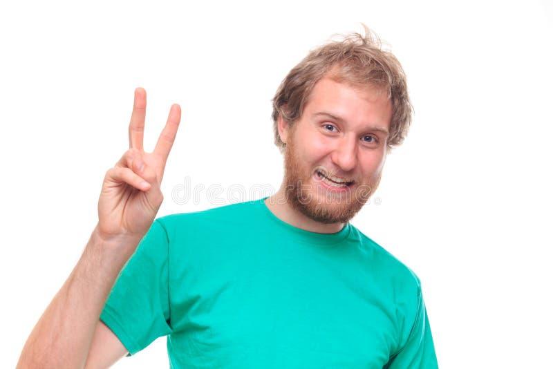 Bärtiger glücklicher Mann, der Siegeszeichen zeigt lizenzfreie stockfotos