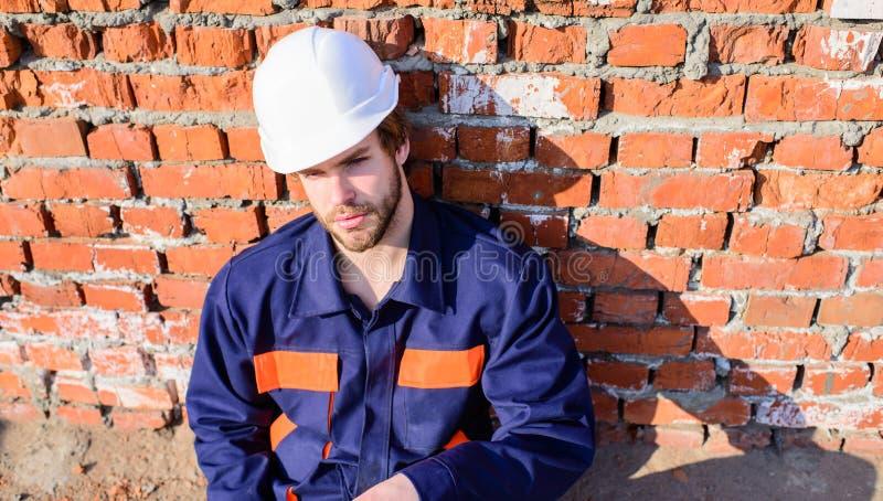 Bärtiger hübscher Erbauer des Kerlschutzhelms Nehmenminute zum sich zu entspannen Mannnehmenbruch-Arbeitstag an der Baustelle stockfotografie