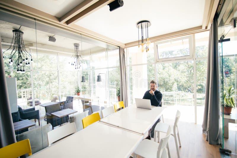 Bärtiger hübscher Geschäftsmann, der am großes Konferenz romm weißen Tisch sitzt und am Laptop bevor dem Treffen arbeitet lizenzfreie stockfotografie