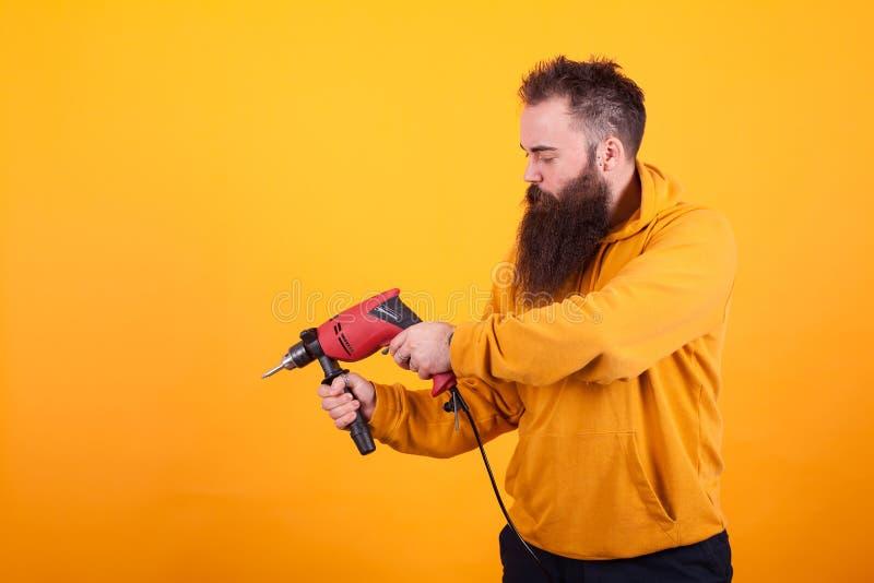 Bärtiger Heimwerker in der gelben Hoodieholdingbohrmaschine über gelbem Hintergrund stockfotografie