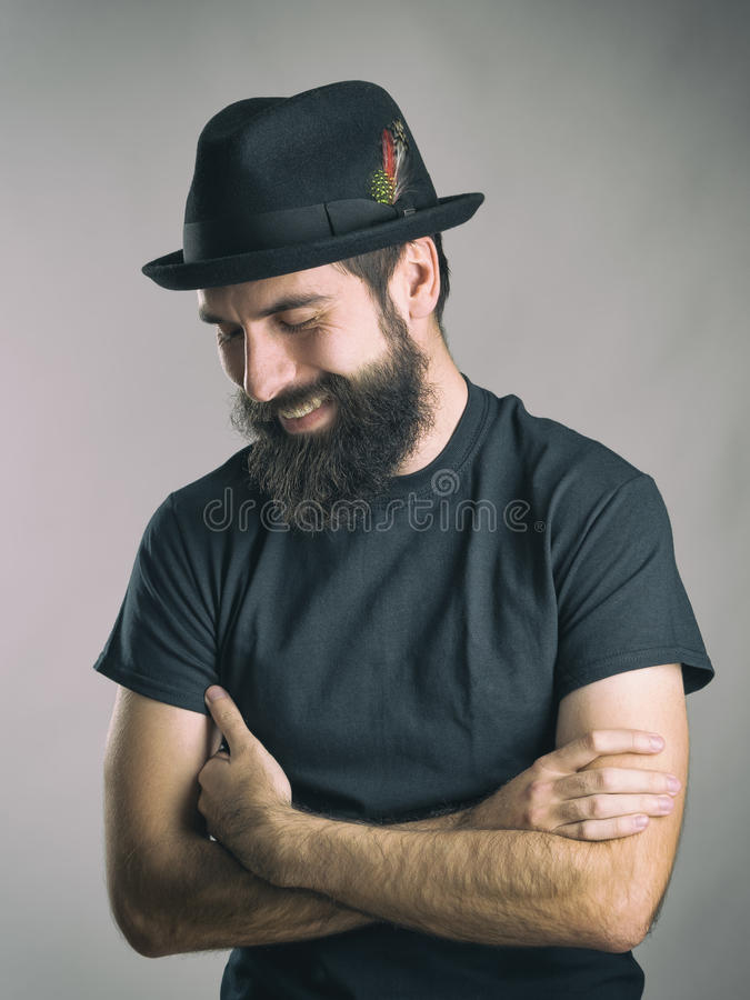 Bärtiger Hippie, der schwarzes T-Shirt und den Hut lacht spontanes unten schauen trägt stockfoto