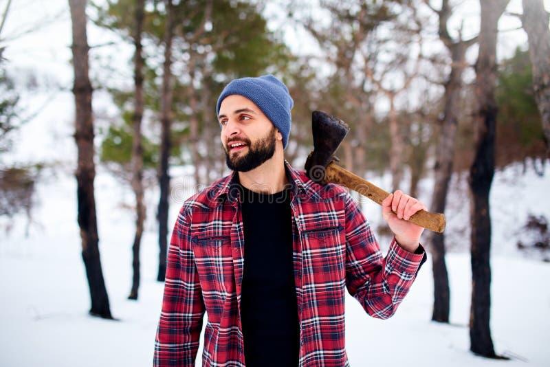 Bärtiger Hippie-Mann in einem schneebedeckten Wald des Winters mit Axt auf einer Schulter Holzfällerstellung in der Waldmannesunt stockfotografie