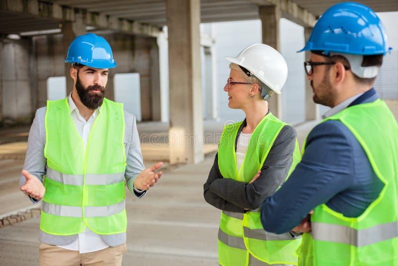 Bärtiger junger Architekt erklärt die Projektdetail- und Zukunftspläne seinen Kollegen stockfotografie