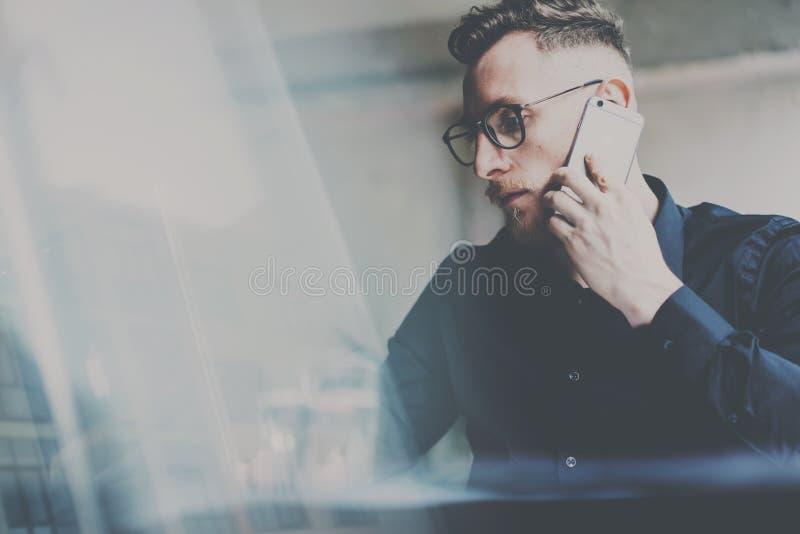 Bärtiger junger Geschäftsmann in den Brillen, die im Büro arbeiten Mann, der zeitgenössischen Laptop und Smartphone für die Herst stockfotografie