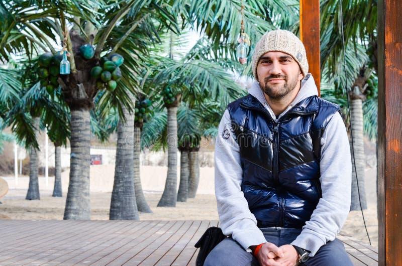 bärtiger junger lächelnder Mann, der auf tropischem Strand mit Palmen sitzt stockfotografie