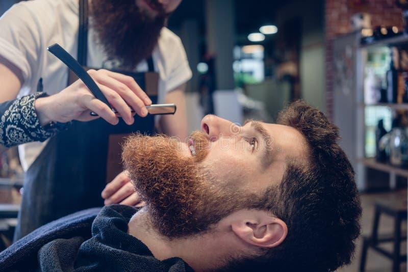 Bärtiger junger Mann bereit zum Rasieren im Friseursalon einer Fähigkeit stockfoto