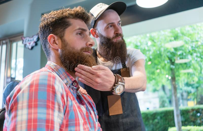 Bärtiger junger Mann, der an eine modische Änderung des Blickes im Friseursalon denkt lizenzfreie stockfotos