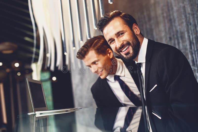Bärtiger junger Mann, der neben seinem Kollegen sitzt und lächelt lizenzfreie stockfotografie