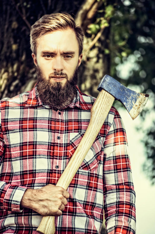 Bärtiger junger Mann im karierten Hemd, das eine alte Axt auf dem Baumnaturhintergrund, im Freien hält stockbilder
