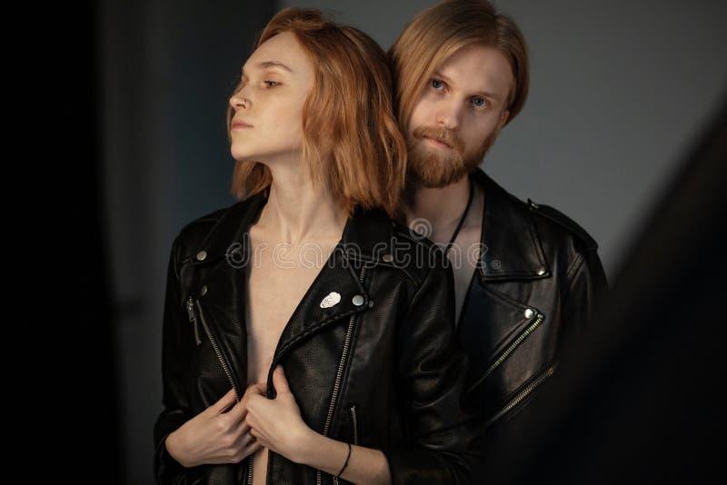 Bärtiger junger Mann mit dem langen braunen Haar in Lederjacke stehendem behinde seine schöne Freundin stockfotografie