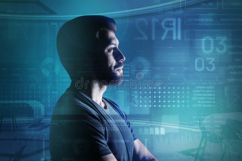 Bärtiger junger Programmierer, der in seinem modernen Büro und in Denken steht lizenzfreies stockbild