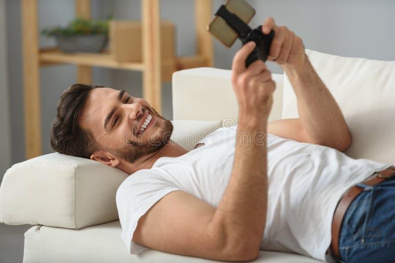 Bärtiger Kerl, der mit Telefon auf einer Couch liegt lizenzfreies stockfoto