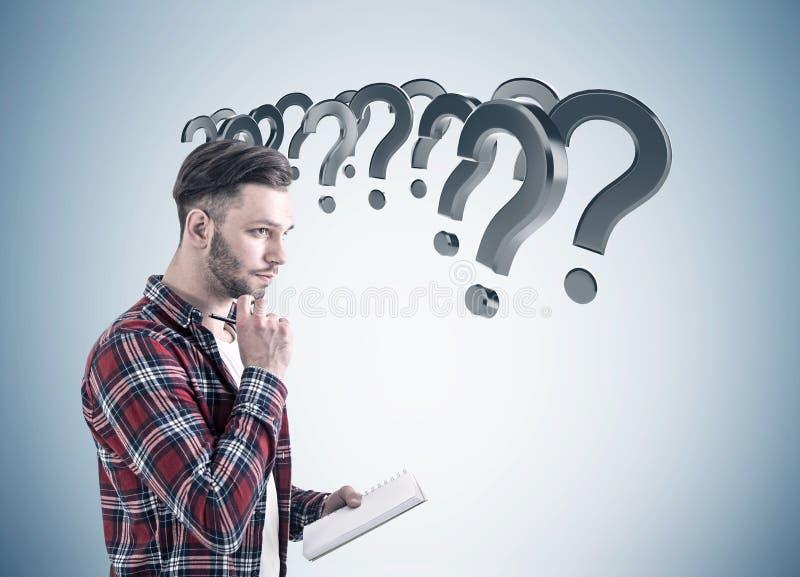 Bärtiger Kerl und graue Fragezeichen lizenzfreies stockbild