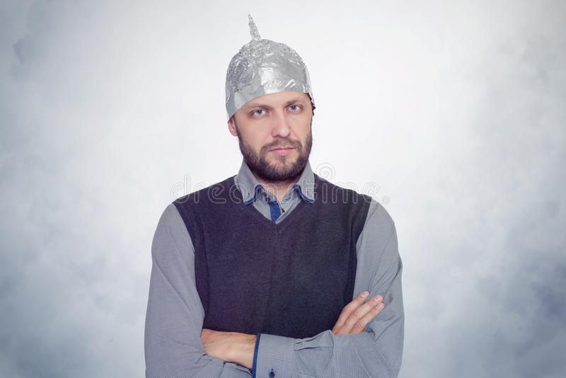 Bärtiger lustiger Mann in einer Kappe der Aluminiumfolie Konzeptkunstphobien stockfoto